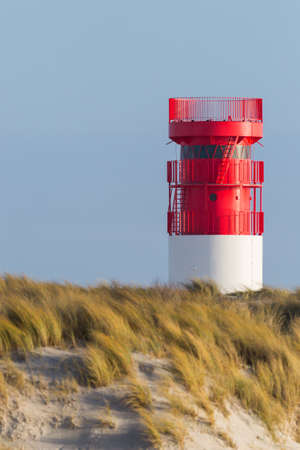 red lighthouse on Helgoland Duene island in blue sky, sand beach in morning sun Imagens
