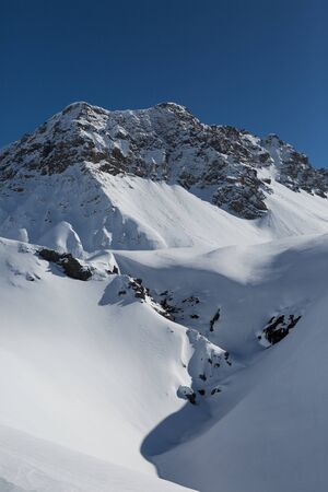 snowcapped Valbellahorn mountain summit near Arosa in winter with snow Imagens