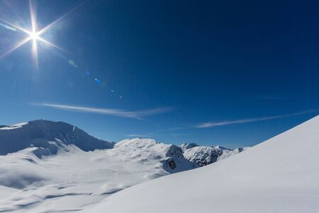 sun and blue sky over Sandhubel mountain near Swiss Arosa in winter landscape Imagens