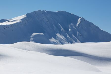 snow covered Sandhubel mountain summit near Arosa in winter, blue sky and sunshine