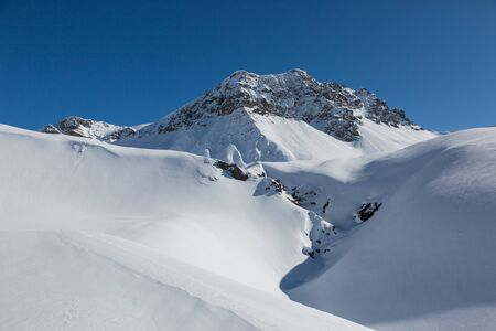 peak of Valbellahorn mountain near Arosa in winter with snow and blue sky