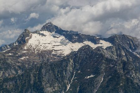 peaks of Swiss Monte Zucchero and Triangolino in Ticino mountains, dark clouds Imagens