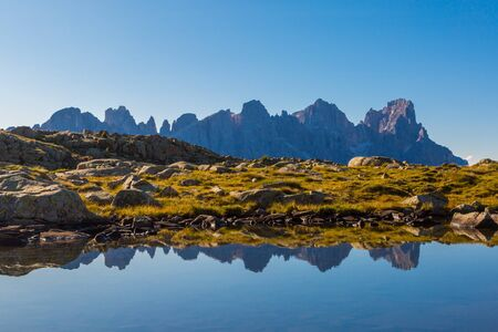 mirrored summits of pala group mountains pale di san Martino with blue sky