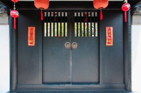 Ancient Chinese black door decorate with hanging lamps