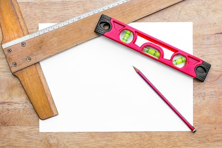 mesure: Building level,T square ruler and pencil with a piece of white paper on a table background Stock Photo