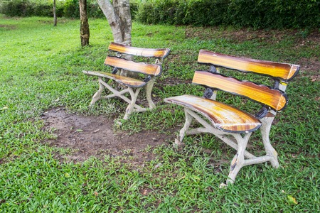 timber bench seat: Concrete bench in wooden striped style in the park