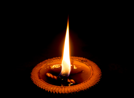 beeswax candle: light candle burning brightly in the black background.Candle light in a pottery tray Stock Photo