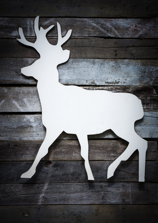 cute white wood reindeer label on plank wooden background