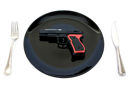 Pistol gun toy in plate with fork and knife isolated on white background.Pistol in plate isolated