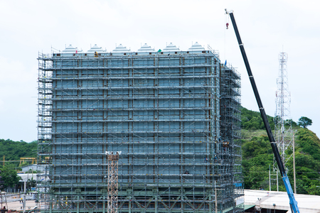 Scaffolding round new building with lift crane with mountain background