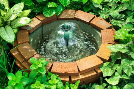 Brick well with fountain decoration in the garden Stock Photo