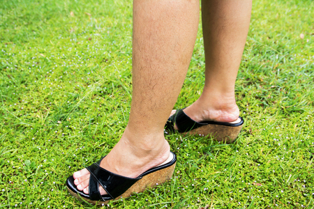 Woman with long hairy leg standing on grass floor