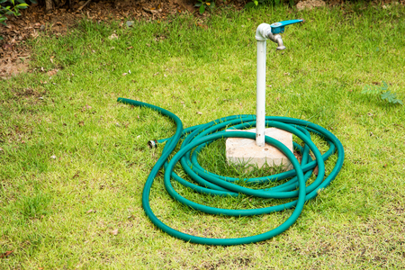 Hose and faucet in the garden background Stock Photo