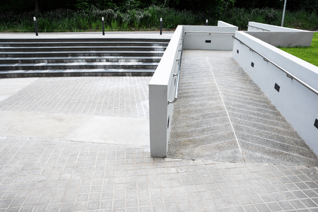 Zigzag ramp for the wheelchair and stairs for normal people adjoining Banco de Imagens