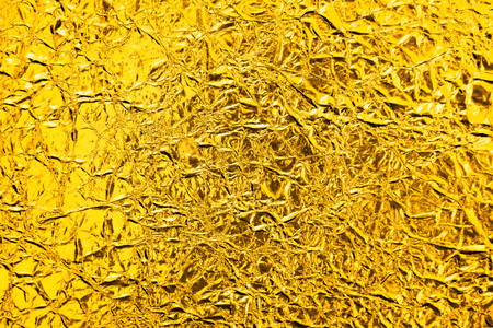 Wrinkle gold foil texture background.Shiny wrinkle gold foil texture