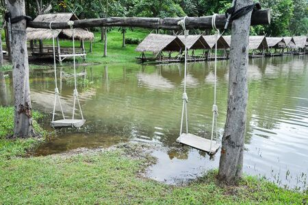 Wood swing with raft beside riverbank at Huay Tung Tao lake background in Chiang mai. Thailand Reklamní fotografie