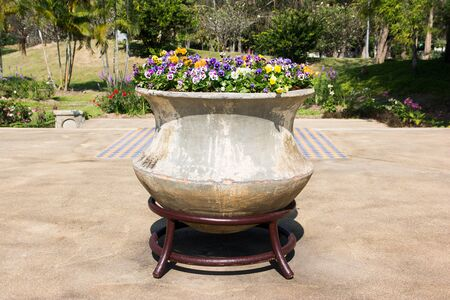 Decoration large pot with flowers in public park background. Big clay pot with decorative flowers and metal stand in the garden