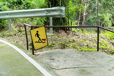 Man on Stairs going down sign symbol beside the street in the park background. Walk down sign with handrail in the garden Stok Fotoğraf