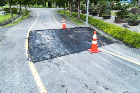 Closed damage patch asphalt road for fixing with traffic cones block in public park background. Damaged asphalt road surface repairing Stok Fotoğraf