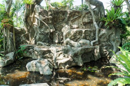 Abandoned old stone waterfall in public park background. Deserted rock waterfall in the garden
