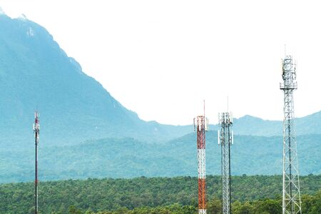 Telecommunication tower antenna with mountain background. Various of mobile telephone communication tower in forest background Stockfoto