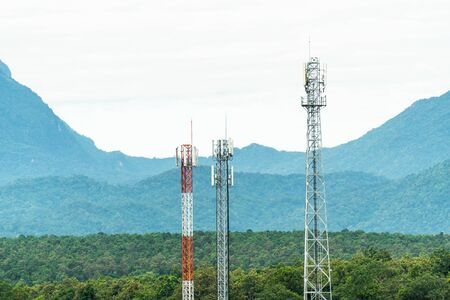 Closeup of telecommunication tower antenna with mountain background. Various of mobile telephone communication tower in forest background Stockfoto