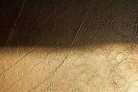 Two tone brown gold leather texture with shadow background. Half dark and bright gold leather texture surface