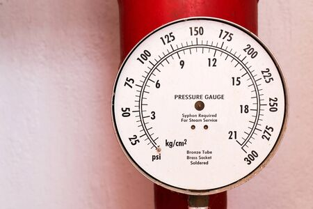 Closeup old water gauge meter with pipe on the wall background. Water pressure gauge dial with red pipe and valve