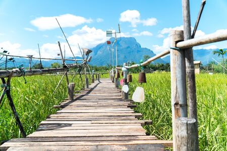 Decoration wood bridge at rice field. Decorative wood bridge with row of hanging bell and pinwheel at green rice field with mountain and blue sky background.