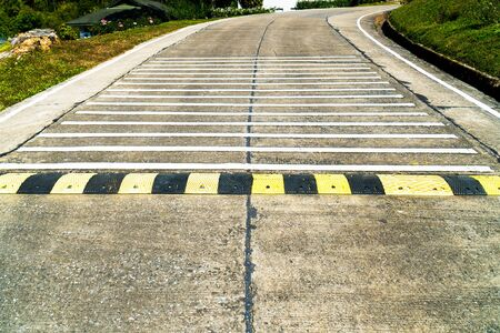 Speed bump road and rumble strip road background. Black and yellow speed bump line road and white rumble strip lines on concrete road surface