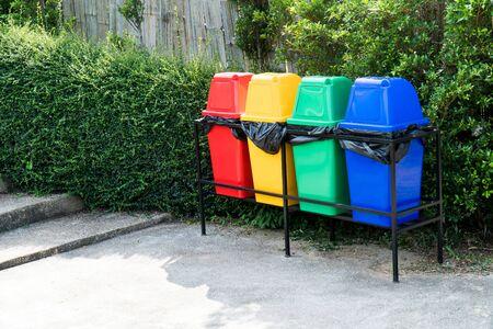 Vari colorato bidone della spazzatura o pattumiera sullo sfondo del giardino. Fila di pattumiera in plastica multicolore nel parco pubblico accanto alla strada e alla scala