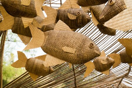 Closeup weave decoration wood fish mobile hanging at public park background. Group woven decorative bamboo wooden fish mobile suspend on wood ceiling roof frame