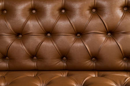 Dark brown leather chair with buttons background. Elegant vintage brown upholstery leather sofa with buttons texture Zdjęcie Seryjne