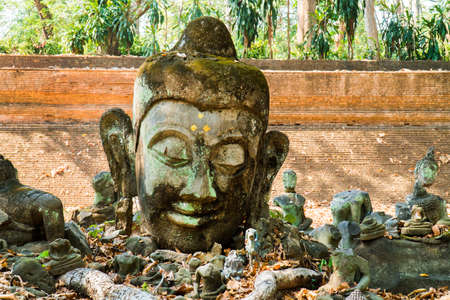 Closeup of damaged buddha image head statue at the temple wall background in thailand. Pile of broken buddha sculpture outdoor at temple monastery Banco de Imagens