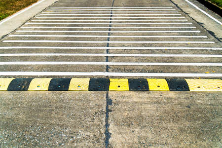 Closeup speed bump road and rumble strip road background. Black and yellow speed bump line road and white rumble strip lines on concrete road surface