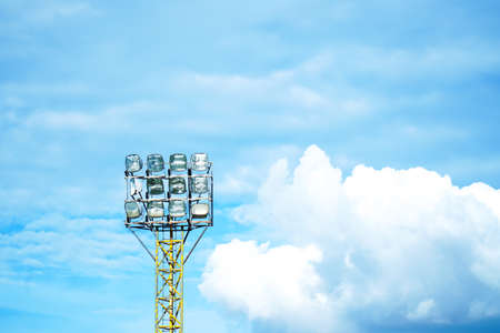 Stadium light pole with light bulb or spotlights with blue sky background. Outdoor soccer or football flood light with high metal stand pillar with blue sky texture Stok Fotoğraf
