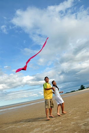 Couple flying kite on beach in thailand photo
