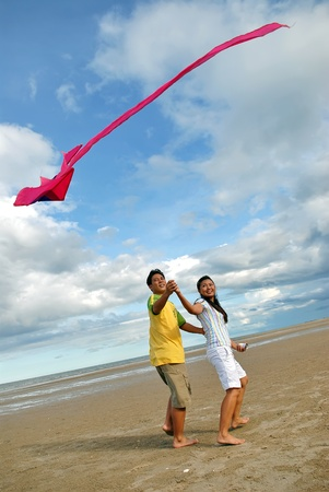 Couple flying kite on beach in thailand Stock Photo - 9845257