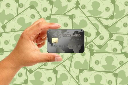 Credit card in human hand with money photo