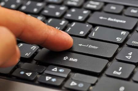 Finger on computer keyboard at enter key photo