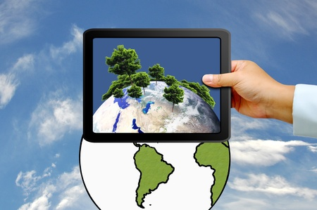 Hand holding tablet PC with  tree on earth globe photo