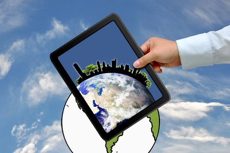Hand holding tablet PC with city on earth globe photo