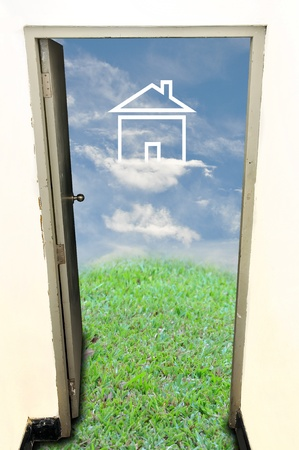 Old door open to green field with house photo