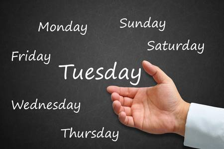 Tuesday Written on Blackboard with hand photo