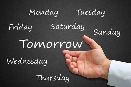Tomorrow Written on Blackboard with hand photo