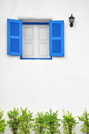 Blue window on white wall photo
