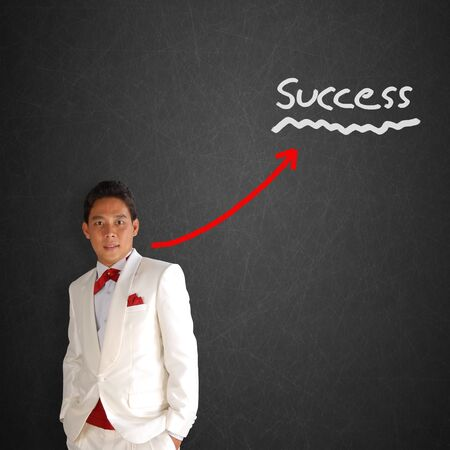 man in a white tuxedo on Blackboard with Business graph Stock Photo