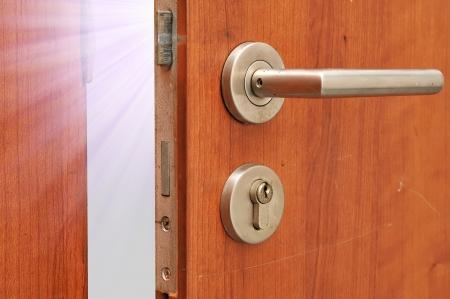 Poignée de porte de style Modren sur la porte en bois naturel avec une lumière blanche Banque d'images