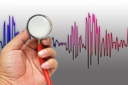 Stethoscope in hand with heart beats cardiogram photo