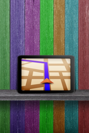 Touchpad gps on the wood shelf and wood wall photo